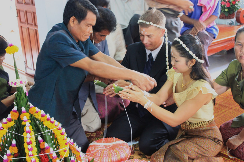 Mother's younger brother,Home, ties string of blessing onto Id's hand.