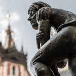 One of Krakow's many bronzes adorns a fountain behind the town hall tower.