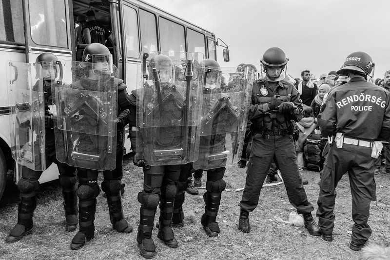 Hungarian police in riot gear prevent refugees from boarding a bus at a holding area outside Röszke on September 5, 2015.