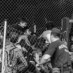 Refugee men, women, and children are corralled into a holding pen by Hungarian police at the Röszke/Horgos border zone on the night of September 14, 2015.