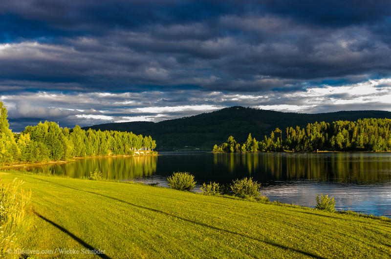 Evening lights on a cloudy summer day on the shore of the Køderen in Buskerud, in Eastern Norway. This photo is published in Lille Ulven Photography's Norway calendars.