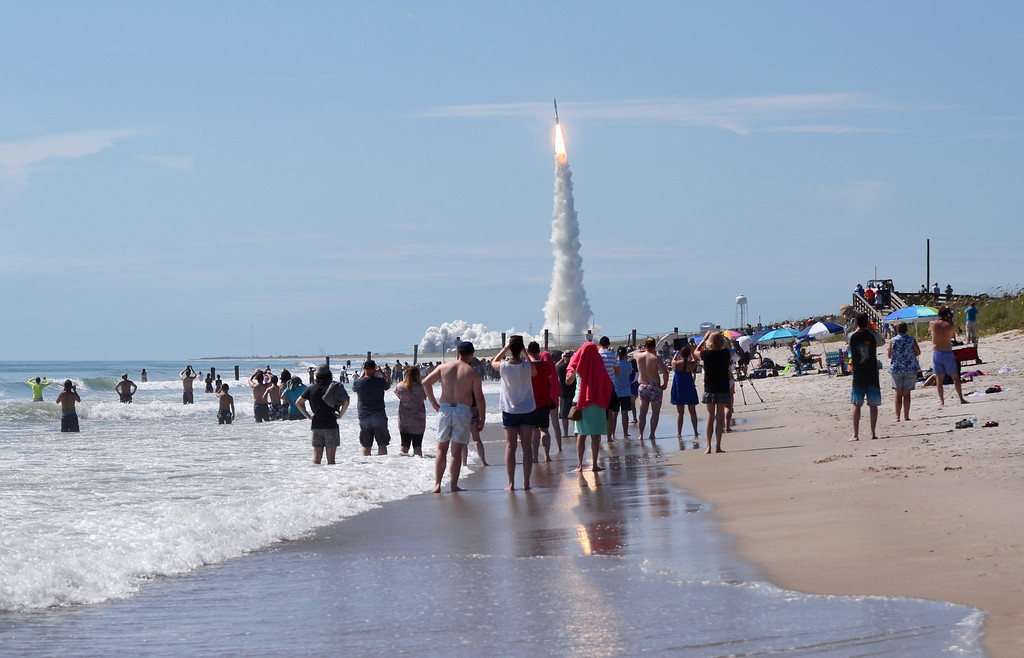 An Atlas V rocket puts on a show for beachgoers as it lifts a massive U.S. Navy satellite into orbit.