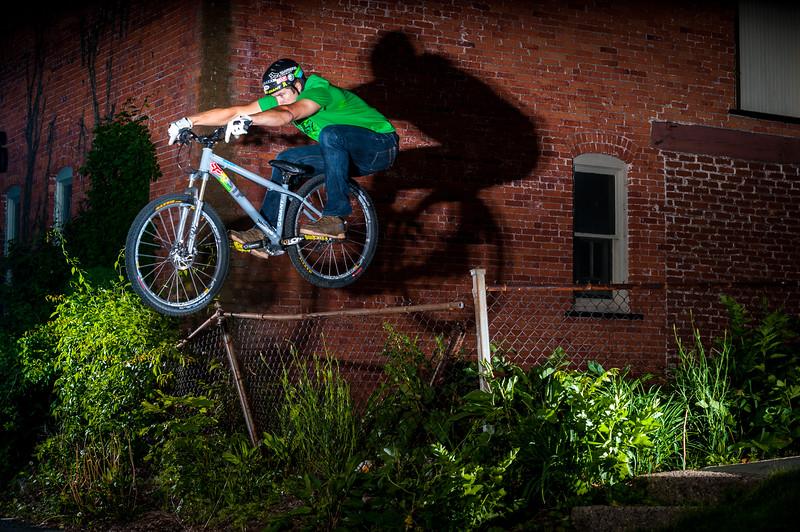 Jeff Lenosky bunnyhops over a fence