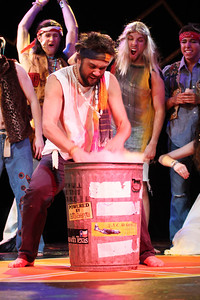 Alex Herzing, a senior Middle Grades Education Major, throws his draft card into the trash can during Pauper Players' production of Hair.