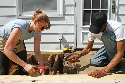 Habitat for Humanity's A Brush With Kindness is working with two  homes in the historic Northside neighborhood this month. Volunteers gathered at the home of Keith Edwards to help repair her porch.  Karen Meyerhoff, a med student at UNC in her last year, and Carl Stewart hammer boards into the porch. Stewart is Edwards cousin and came out to work on the porch starting at 8am. Meyerhoff, who is in her last year of med school, said she has a lot of free time since entering her last year and decided to volunteer.