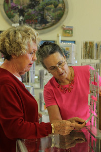 Loyal Womancraft Gifts patron, Edna Webster, (left) and Karen Graves, Display Chair, (right) discuss a jewelry purchase.  Webster loves the atmosphere of the store, the ladies are very helpful and the prices are reasonable.  Graves has been working at Womancraft Gifts since 1976 and loves the work environment said it was great way to learn and share with other artists.