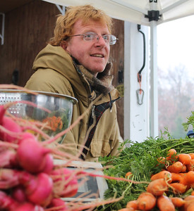 Ben Bergmann, a vendor from Fickle Creek Farm in Efland, sells fresh produce, pastured eggs and pasture-raised meats at the Chapel Hill Farmer's Market. On Tuesday November 26, he weathered the rain and cold to supply his clients with cooking tips and the necessities, including turkeys, for Thanksgiving. The Farmer's Market is located outside at University Mall.