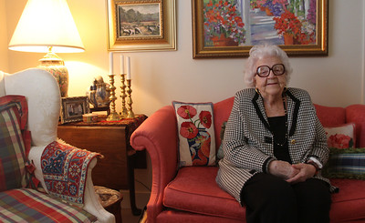 "Maggie Love, 88, paints ""happy paintings"" that are now on display at University Mall. She has macular degeneration and is starting to lose her eyesight, which makes painting more difficult. She continues to paint and now does more abstract work. Love poses with her artwork in her home at Galloway Ridge retirement community at Fearrington."