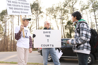 "John Pinkerton (left) of Chapel Hill and John Greifenberger (middle), a Chapel Hill racquetball player of 35 years, protest the destruction of the Chapel Hill YMCA's racquetball/handball courts by informing Azamat Ahmedjanov, 16 from Chapel Hill. ""The board seems to be discriminating against seniors who play racquetball and handball players,"" argued Greifenberger. He and his fellow protestors enjoy playing racquetball with each other and ""they're trying to take it away,"" said Pinkerton."