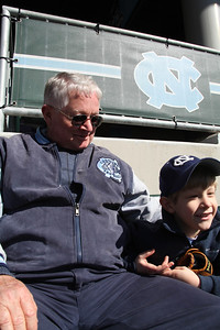 Carson West, 5, watches the UNC baseball game Sunday with his grandfather Eddie West.  Eddie, a long-time Carolina baseball fan, comes to almost all of the games and always brings one of his grandchildren with him.