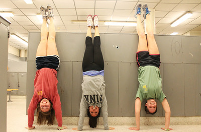 From left. Lauren Hamlett, Hilda Tajalli, and Andrea Lambert find temporary relief for their feet by doing hand stands.