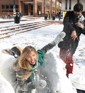"Grad student, Asadullah Naweed throws snowballs at sophomores Cyara De Lannoy and Cassy Karlsson. ""You can't hit us, we have a fort for protection!"" Karlsson said.  The girls had been taking shifts guarding their fort all day, because people had been trying to take it."