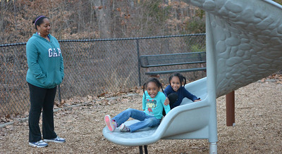 Shantina Foster watches her daughters Catherine Thorpe (in navy) and Kaelyn Thorpe (in light blue) play at Hank Anderson Park in Carrboro.