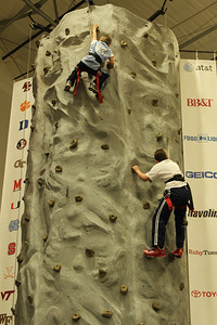 Kids climbing a rock wall at the ACC Fan fest before the championship game