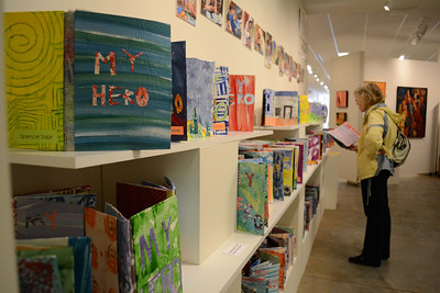 "FRANK gallery exhibit, ""Meet Our Heros"" displays the work of Durham Academy 6th grade students. The students created pop-up books that tell the story of their heroes. Ridna Frasbergen looks at one of the books created by her grandson's classmate."