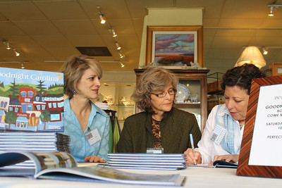 Elaine O'Neil, left, Marie Myers Lloyd and Missy Julian Fox sign copies of their book, Goodnight Carolina, at Peacock Alley Saturday morning. Marie and Missy wrote the book together while Elaine created the textile illustrations.