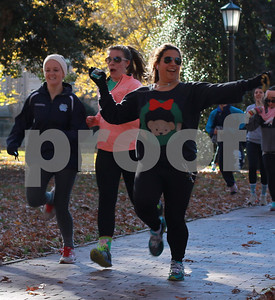 "Natalia Perez runs the Tri Sigma Tacky Holiday Sprint in McCorkle place on Sunday afternoon.  ""The Sprint benefits the Sigma Sigma Sigma foundation, which goes towards scholarships for women and play therapy rooms in hospitals, like the one at UNC,"" said the Delta Delta chapter's president, Emily Bell."
