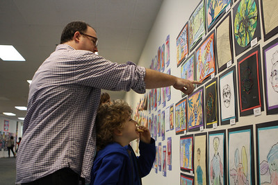 Patrick Herron and his son, Booker, 7, look at the student created artwork on display at University Mall on Saturday. Booker is a student at Estes Hill Elementary School.