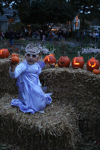 Fearrington Village celebrated its annual Pumpkin Fest on Tuesday night. The village center was filled with jack-o-lanterns and stores were open late for Halloween festivities, including spooky stories for children at the bookstore. Alli Peterson, 3, of Cary, poses with some pumpkins in her princess costume.