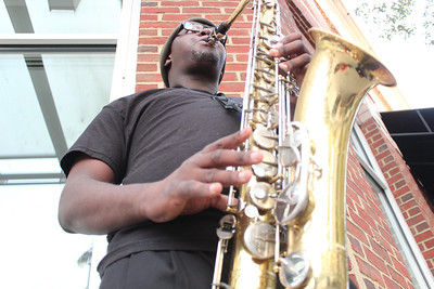 "Jesse Rainey III plays the saxophone in front of the Ackland Museum gift shop on Franklin Street. He is a part of a musical group called the ""Sagging Naturals"" that play at the Franklin Hotel. ""I play on Franklin Street to provide free music and get our group noticed,"" says Rainey."