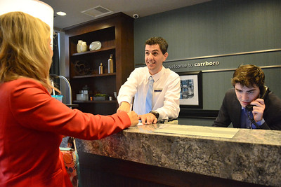 Hampton Inn & Suites General Manager Kevin Rooney talks with Katie Henning, Sales Manager, while Jack Bowen, Front Desk Agent, takes calls.