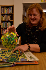 Christy Cherney admires one of the elaborate and detailed books in the library's pop-up collection. There will be an exhibition and event in Wilson Library today beginning at 5pm. Three pop-up book collectors will come to show their collections alongside the library's own.