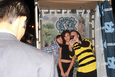 (from left to right) James Ross, Brooke McKenna, and Luke Neeman pose in a selfie booth on East Franklin Street.