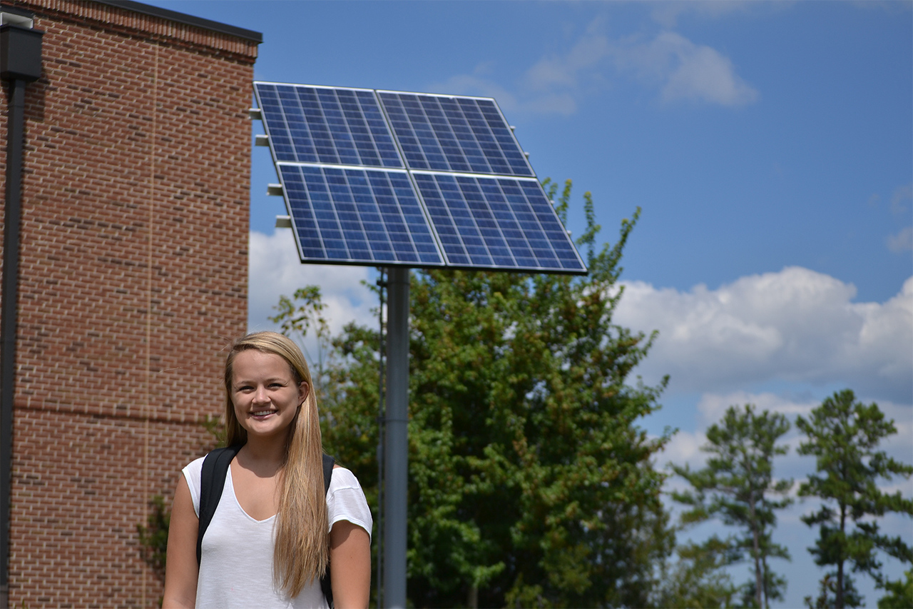 Solar panels were installed on the grounds of Carrboro High School this August. Current seniors Holly Gallagher and Jocelyn Buckley led the project with help from Dan Schnitzer, the sustainability coordinator for local school systems, after being inspired by their AP Environmental Science class last school year. Holly (age 17) poses with the first solar panel of what she hopes is more to come on Thursday afternoon Sept. 17.