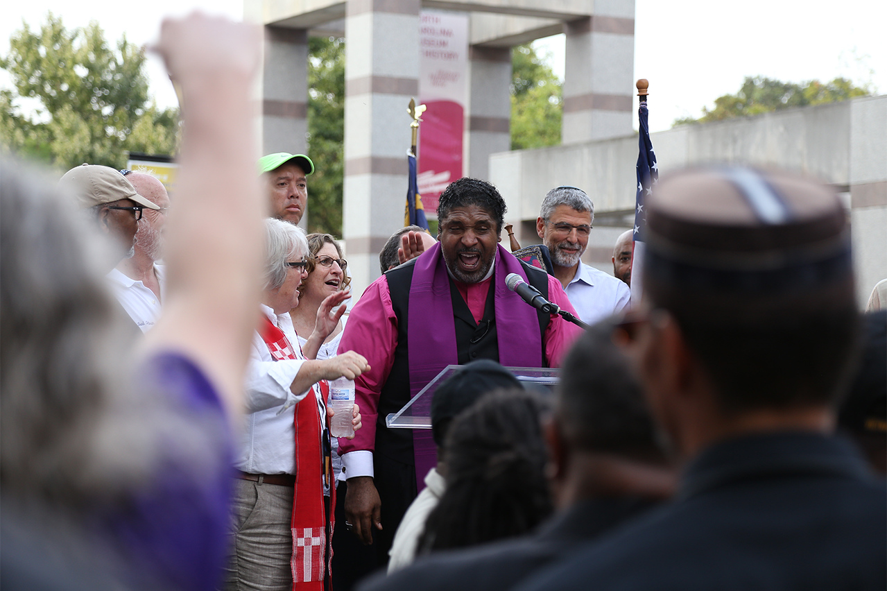 """Rev. Dr. William J. Barber II speaks about the history of voters' rights in the U.S. at the rally on Thursday.   The NAACP lead a march and rally in Raleigh on Thursday as part of """"America's Journey for Justice,"""" a 806-mile march from Selma, Alabama, to Washington D.C. Hundreds gathered in the Bicentennial Plaza to protest for voters' rights."""