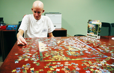 the SECU house is a house with the University Hospitals where families can stay if they have a long commute when one of their loved ones is in the hospital. It recently had its 100,000th guest.  Guest Alex Lee works to finish a puzzle started by other guests.