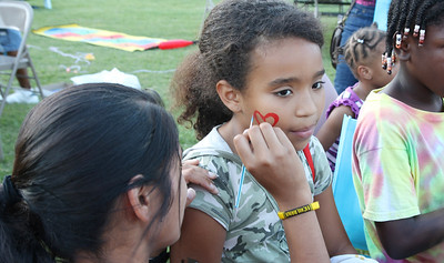 Daisy Kaur (Junior - volunteering with Omega Phi Beta) paints a heart on Grady Grant's face at the Northside Block Party.  (Far right: Kiara Shaw)