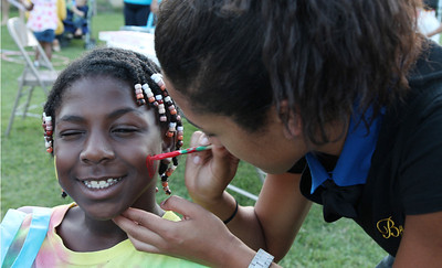 Carissa Davis (Omega Phi Beta) face painting Kiara Shaw at the Northside Block Party.