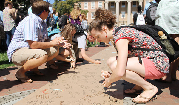 Senior Isabella Cassell, a psychology major from Dartmouth, MA, signs a petition at a rally in support of Holden Thorp. The rally took place in front of South building on Friday afternoon.