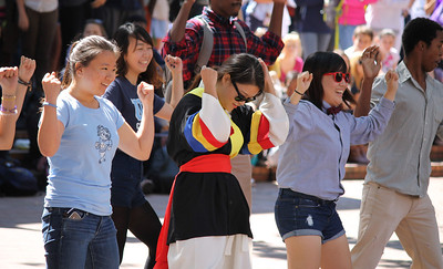 "The Korean American Student Association (KASA) organized a Gangnam Style flash mob in the pit. Soobin Seong, a junior Global Studies major (left), Seung Hui Choi, a junior economics major (middle), and Inhye You, a senior chemistry major (right), began the ""horse riding dance,"" and hundreds of students joined later."