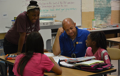 Chuck Hennessee, an AVID teacher at Culbreth Middle School, helps his students with their assignments. Today the students are their own tutors. Each student identifies a subject that they need to study and are put into groups. Hennessee points out that he does not teach his students; his students teach each other.
