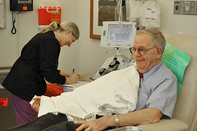Al Whitney, 77, jokes with phlebotomist Stephanie Anthony as he donates his 750th unit of platelets at the Blood Donation Center at UNC Hospitals on Tuesday morning. Whitney has donated platelets in all 50 states and three countries.