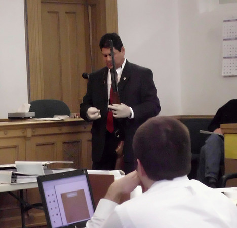 Seth Techel observes crime lab firearms expert Victor Murillo, holding what he testified is the murder weapon. Techel stands accused of murdering his wife and unborn child. <br /> Mark