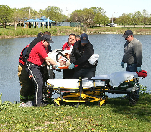 Mark Newman/The Courier<br /> Rescuers pull a woman from the water Friday morning after she fell, struck her head and rolled into the lagoon. The day was one of the coldest in weeks.