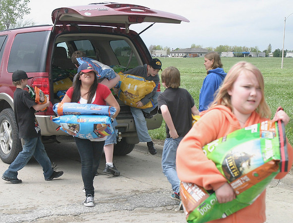 Mark Newman/The Courier<br /> Fifth-graders from Douma Elementary School unload the pet food donations from their food drive at South HyVee on Saturday. The donations filled an entire section of the Heartland Humane Society's storage area.