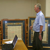 Mark Newman/The Courier<br /> Gary Stephenson of Fort Dodge shows Wapello County supervisors a framed, 1930s  print of the U.S. Constitution. So far, between him and late father,  the document hangs in 73 of the 99 county courthouses in Iowa.