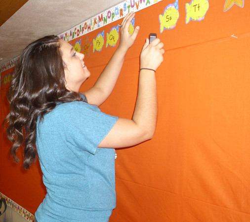 """Jenna Wilkins, the new second-grade teacher at Agassiz Elementary School, arranges the """"word wall"""" in her classroom on Wednesday. She says children should not worry about school, as they will soon make plenty of friends they can see every day."""