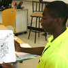Ottumwa Job Corps student Jamal Robinson, 17, of Omaha Nebr. flips through his portfolio Friday which contains superheroes, original cartoon designs and this self-portrait, complete with energy boost from a big mug of coffee.