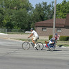 """Flynn Donoho and his traveling companion """"Diva"""" the dog ride through Ottumwa Monday on their way to Highway 34 West. The California man is on his way to the next state after a cross country bike ride to raise money for cancer research."""