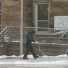 A county worker sprinkles salt outside of the Wapello County Courthouse early Thursday.