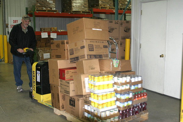Rodger Graham, an Experience Works associate at the Southeast Iowa Food Bank, moves some of the food that has come in. Area residents have been donating food and cash in order to restock the shelves at the charitable orginization. <br /> Mark Newman