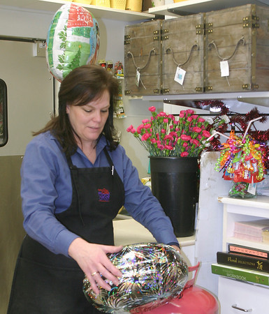 Judy Mathis, Hy-Vee North floral department manager, inflates a helium balloon on the Sunday prior to New Year's Eve, 2012. Though prices have risen sharply, independent Ottumwa florists say you'd be lucky to get any helium balloons at all