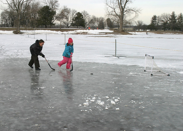 Jason, 10, and Karen Rukgaber, 6, slap one into the net while playing ice hockey at Ottumwa Park Sunday afternoon. The ice was thick and the air was fairly warm — something their mom said was expected to change soon.