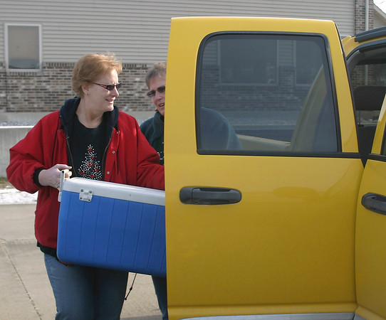 Bee Hamre and her sister Rosezelma Funk load food into their vehicle Tuesday. For the past few years, they've spent Christmas Day delivering meals to those who request them from the Masons.