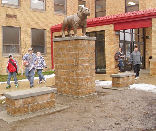 The new bulldog sculpture guards the entrance to Evans Middle School after classes Thursday. Two retired teachers are seeing to some long-term improvements around the school.<br /> Mark Newman
