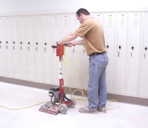 Mark Newman/The Courier<br /> Tom Walls uses a machine with a sandpaper bottom to remove the top layers of wax Friday from the floors at Ottumwa High School. Later, a good scrubbing needs to be done before new wax can be put on.
